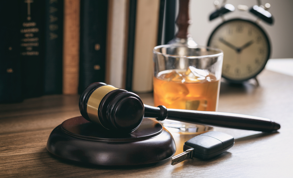 gavel, car keys and glass of alcohol