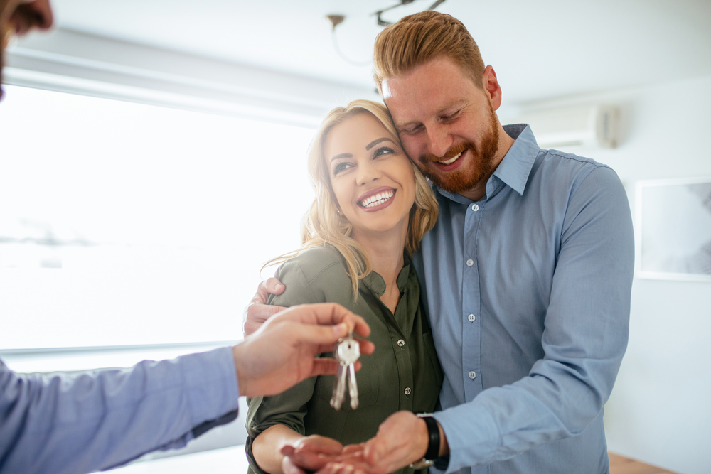 happy couple being handed keys to their home