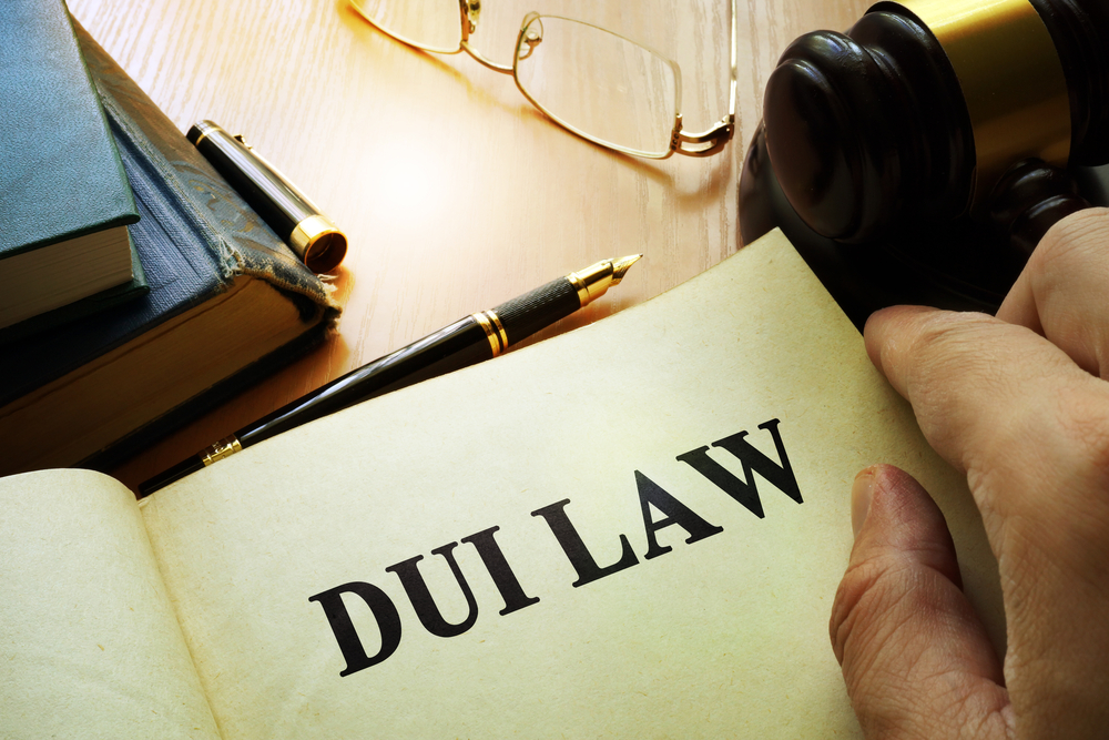 DUI Law printed on a document next to gavel, glasses, pen and books