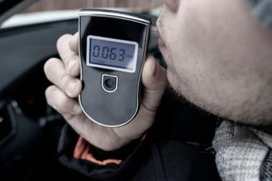a man with a breathalyzer in the car